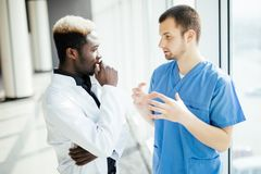 Mixed race Two doctors discussing results of the analysis in modern hospital. Two doctors discussing results of the analysis in hospital stock images