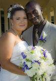 Mixed race wedding couple. Half body portrait of black groom with smiling Asian bride holding bouquet of flowers Royalty Free Stock Photography