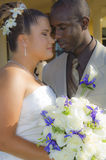 Mixed race wedding couple faces. A  close-up of a mixed race wedding couple with faces together and eyes closed holding bouquet of flowers Stock Image