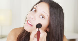 Mixed race woman applying makeup on face Stock Photo