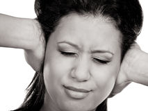 Mixed race woman closing ears with hands. Royalty Free Stock Photography