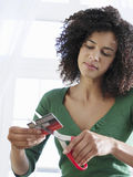 Mixed Race Woman Cutting Credit Card Stock Photo
