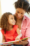 Mixed race woman and daughter reading Royalty Free Stock Images