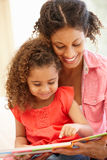 Mixed race woman and daughter reading Stock Photo