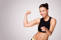 Mixed race woman demonstrating biceps. Cheerfully smiling mixed race sporty woman demonstrating biceps, isolated on white background royalty free stock photos