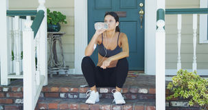 Mixed race woman drinking water after jogging Royalty Free Stock Photos