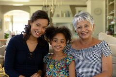Mixed race woman with her senior mother and her young daughter looking at camera