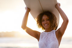 Mixed-race woman holding a surfboard at sunset. Young mixed-race woman holding a surfboard above her head at sunset at the beach Royalty Free Stock Image