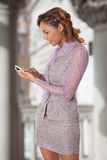 Attractive business woman uses her smart phone. Mixed race woman interacts with her cell phone Royalty Free Stock Images