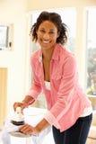 Mixed race woman ironing Stock Image