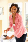 Mixed race woman ironing Stock Photography