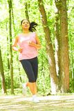 Mixed Race Woman Jogging In Forest Stock Photography