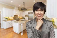 Mixed Race Woman Looking Back Over Shoulder Inside Custom Kitchen royalty free stock image