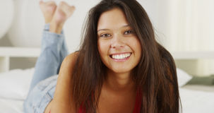 Mixed race woman lying on bed smiling at camera Stock Photography