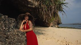Mixed race woman model during vacation on tropical island. Sexy sensual lady in Red Dress posing on the Beach. Slim