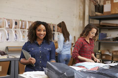 Mixed race woman packing clothing orders smiles to camera. Mixed race women packing clothing orders smiles to camera Royalty Free Stock Photography
