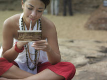 Mixed Race Woman Reading Postcard Outdoors. Young mixed race woman sitting on rock and reading postcard Royalty Free Stock Photo