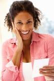 Mixed race woman receiving good news Stock Photo