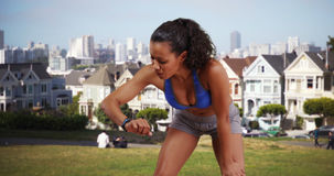 Mixed race woman runner looking at her fitness watch at the park Stock Image