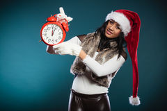 Mixed race woman in santa hat with alarm clock. Royalty Free Stock Photos