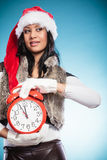 Mixed race woman in santa hat with alarm clock. Stock Photography