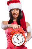 Mixed race woman in santa hat with alarm clock. Royalty Free Stock Photography
