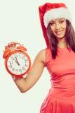 Mixed race woman in santa hat with alarm clock. Royalty Free Stock Photos