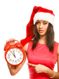 Mixed race woman in santa hat with alarm clock. Stock Photo