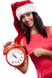 Mixed race woman in santa hat with alarm clock. Stock Image