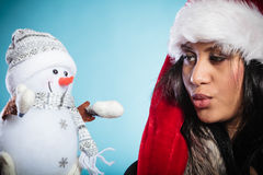 Mixed race woman in santa hat with little snowman. Royalty Free Stock Photos