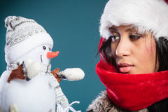 Mixed race woman in santa hat with little snowman. Stock Photos