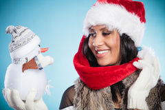 Mixed race woman in santa hat with little snowman. Royalty Free Stock Photography