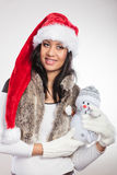 Mixed race woman in santa hat with little snowman. Royalty Free Stock Photo