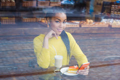 Mixed race woman sitting in a coffee shop with her latte drink Royalty Free Stock Photo