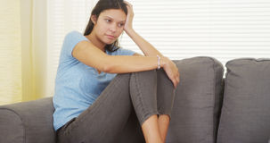 Mixed race woman sitting on couch thinking Stock Photo