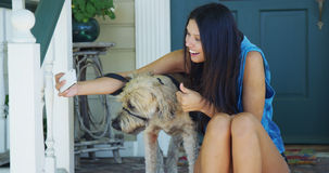 Mixed race woman sitting on porch taking pictures with dog Stock Image