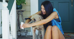 Mixed race woman sitting on porch taking pictures with dog stock photos