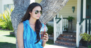 Mixed race woman standing by tree drinking iced tea Stock Image