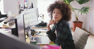Mixed race woman tapping on computer in creative office