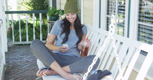 Mixed race woman texting and drinking tea on porch Royalty Free Stock Photography