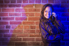 Mixed Race Woman Using Her Cell Phone Against Brick Wall Stock Photography