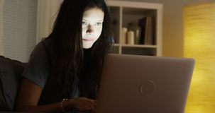 Mixed race woman using laptop at night Royalty Free Stock Images