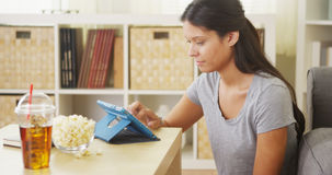 Mixed race woman using tablet on coffee table Stock Image