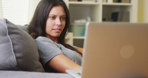 Mixed race woman watching horror show on laptop Royalty Free Stock Images