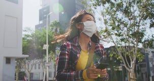 Mixed race woman wearing medical coronavirus mask on the street