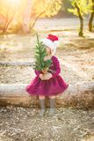 Mixed Race Young Baby Girl Having Fun With Christmas Tree. Cute Mixed Race Young Baby Girl Having Fun With Santa Hat and Christmas Tree Outdoors On Log royalty free stock images