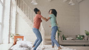 Mixed race young beautiful girls dancing on a bed together having fun leisure in bedroom at home stock video