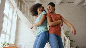 Mixed race young beautiful girls dancing on a bed together having fun leisure in bedroom at home Royalty Free Stock Images
