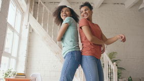 Mixed race young beautiful sisters dancing on a bed together haveing fun leisure in bedroom at home stock video footage
