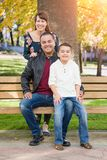 Mixed Race Young Couple with their Son on a Park Bench. Mixed Race Young Family Portrait At The Park stock photo